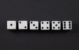 Tärningen som visar, numrerar i rad en till sex Arkivbild