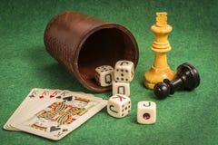 Tärningkopp med däckkort och schackstycken Arkivfoto