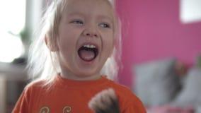 tät flicka little upp Baby målar hennes framsida med en rodnadborste arkivfilmer