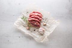 tät meatpork för bakgrund upp white Grisköttslieces med vitlökpeppar och rosmarin på vit Royaltyfri Fotografi