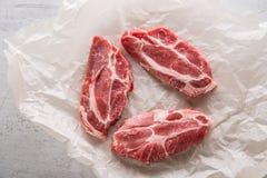 tät meatpork för bakgrund upp white Grisköttslieces på vit conkretebakgrund Royaltyfri Bild