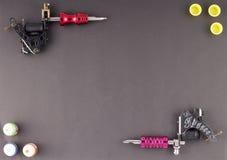 Tätowieren Sie Maschinen mit drei Flaschen Tinte und drei Tintenbehältern auf braunem Hintergrund stockbild