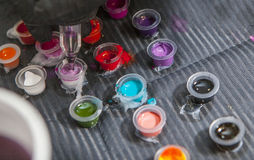 Tätowieren Sie mischende Farben des Künstlers in kleine Schale für Tinte stockfotos