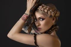 Tätowierte Blondine mit Pythonschlange auf grauem Hintergrund lizenzfreie stockfotos