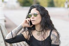 Tätowierte Frau, die auf Bank sitzt und telefonisch in der Straße spricht Lizenzfreie Stockfotos