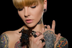 Tätowierte junge Frau mit Tätowierungsmaschine Stockbild