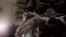 Tätowierte muskulöse Hände eines klatschenden Talkumabschlusses des Mannes oben in der Zeitlupe stock footage