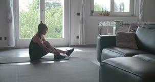 Tätowierte sportliche Frau, die zu Hause ihre Schuhe vor Eignungstraining bindet Inländisches Training des Wohnzimmers Zeitlupe 4 stock video footage