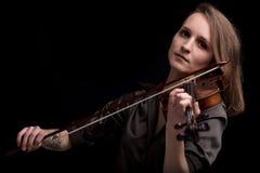 Tätowierte Violinistfrau, die im schwarzen Hintergrund spielt Stockfotos