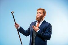 Tätowierter bärtiger Mann in einer Klage, die Stock hält Lizenzfreie Stockfotografie