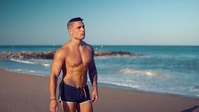 Tätowierter sexy männlicher Trainer des Bodybuilders am Strand stock video footage