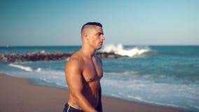 Tätowierter sexy männlicher Trainer des Bodybuilders am Strand stock video