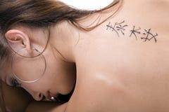 Tätowierung auf einer Rückseite der jungen Frau lizenzfreie stockfotos