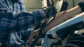 Tätowierung wird auf einer männlichen Armprothese gemacht stock footage