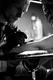 Tätowierungskünstler, die Tätowierung machen Meister arbeitet auf Berufsmaschine und in den sterilen schwarzen Handschuhen Stockfoto