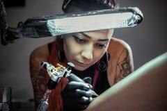 Tätowierungsmeister bei der Arbeit Frauentätowierungsmeister im Prozess der Schaffungstätowierung unter dem Lampenlicht Lizenzfreie Stockbilder