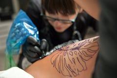 Tätowierungsmeister des jungen Mädchens bei der Arbeit Stockfotografie