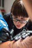 Tätowierungsmeister des jungen Mädchens bei der Arbeit Stockfotos