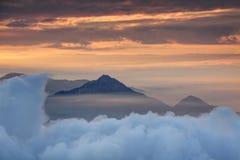 Tätt molnlager med det koniska maximumet och orange morgonmist fotografering för bildbyråer