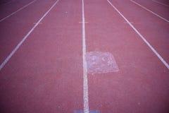Tätt upp, har det röda rinnande spårgolvet vita linjer i den utomhus- stadion för bakgrunden arkivbild