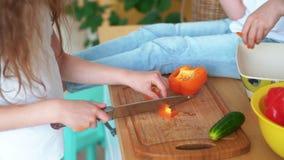 Tätt upp, hjälper flickan som snitt pepprar på kökbrädet, syster, henne, ultrarapid arkivfilmer
