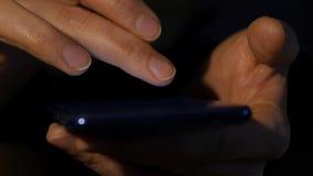 Tätt upp kvinnors använder fingrar smartphonen i natten flicka som bläddrar internet på en mobiltelefon långsam rörelse lager videofilmer