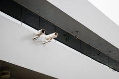 Tätt upp till två säkerhetskameror på strukturen av en byggnad med en stor spegel ovanför dem arkivfoton
