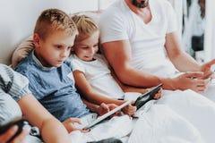 Tätt upp två ungar som spenderar morgon med minnestavlor royaltyfri fotografi