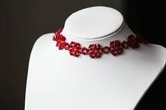 Tättsittande halsbandhalsband i formen av blommor i rött Arkivbilder