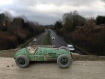 Tävlings- bil för tappningleksak, grönt slitet målarfärgslut upp, sett från ovanför en suddig bakgrund för huvudvägen arkivbild
