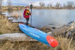 Tävlings- stå upp paddleboarden på en lugna sjö Arkivfoto