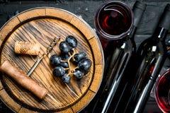 tła szkła czerwone wino Czerwone wino z winogronami i starą baryłką zdjęcia stock