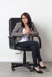 Tålmodig affärskvinna som i regeringsställning poserar stol för hennes start-up jobb royaltyfri foto