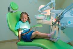 Tålmodig flicka för sunda tänder som väntar i tand- stol i tandläkare av Royaltyfri Fotografi