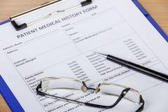 Tålmodig form för medicinsk historia på skrivplattan med pennan och glasögon arkivbild