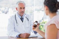 Tålmodig innehavkrus av medicin arkivfoto