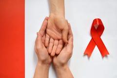 Tålmodig service med diagnos av HIV-HJÄLPMEDEL Kvinnors händer som rymmer handen Världen bistår dag och det röda bandet dåliga ny royaltyfria bilder