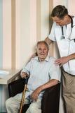 Tålmodiga sjukvårdarbetare och åldring Arkivbild