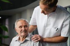 Tålmodiga sjukvårdarbetare och åldring Fotografering för Bildbyråer