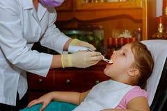 tålmodigt gladlynt barn med lockigt hår flicka som ler i dentist& x27; s-stol barnmunsned boll som är öppen i dentist&en x27; s-s arkivbild