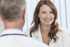Tålmodigt möte för lycklig kvinna med den manliga doktorn i regeringsställning royaltyfri foto