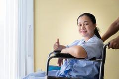 Tålmodigt sitta i en rullstol med bra uppmuntran royaltyfri foto