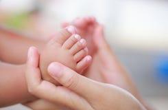 Tår för barn` s i omfamningen av moderhänder royaltyfria foton