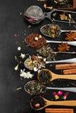 Tè aromatico del fiore in cucchiaio su fondo nero rustico Fotografia Stock