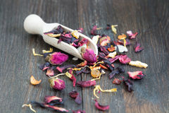Tè asciutto con i petali e le erbe in cucchiaio di legno Fotografia Stock