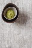 Tè asciutto di Matcha in un piccolo piatto marrone Fondo di legno grigio top Immagini Stock