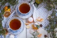 Tè in belle tazze della porcellana Mattina del ` s del nuovo anno Mandarini e tazze di tè su un fondo di legno bianco Vista super Immagini Stock