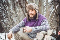 Tè bevente dell'uomo barbuto nella foresta Immagini Stock