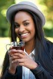 Tè bevente della bella ragazza nera all'aperto Immagini Stock