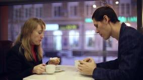 Tè bevente della donna e dell'uomo nel caffè archivi video